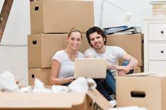使用膝上型计算机的微笑的夫妇,当移动房子时 库存照片