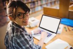 使用膝上型计算机的微笑的女学生在图书馆 免版税库存照片