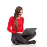使用膝上型计算机的微笑的女学生 免版税库存照片