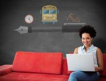 使用膝上型计算机的微笑的女性大学生的综合图象,当坐沙发时 库存图片