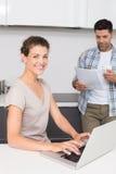 使用膝上型计算机的微笑的妇女,当伙伴读报纸时 免版税库存图片