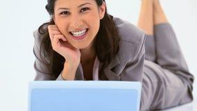 使用膝上型计算机的微笑的妇女,当说谎时 免版税库存图片