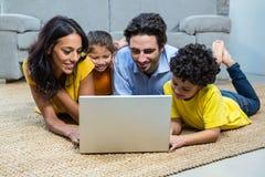 使用膝上型计算机的微笑的家庭在客厅 免版税库存照片