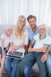 使用膝上型计算机的微笑的家庭在他们的客厅 库存照片
