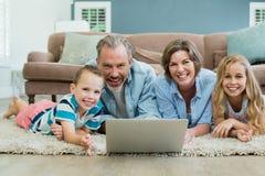 使用膝上型计算机的微笑的家庭,当说谎在地毯在客厅时 免版税库存图片