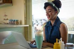 使用膝上型计算机的微笑的少妇,当食用奶昔时 免版税库存照片