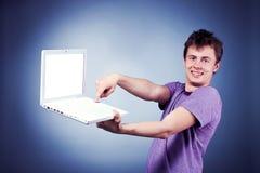 使用膝上型计算机的微笑的年轻人 库存照片