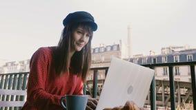 使用膝上型计算机的微笑的愉快的典雅的女实业家,看在早餐的埃菲尔铁塔在田园诗巴黎早晨阳台 股票录像