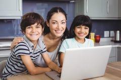 使用膝上型计算机的微笑的母亲和孩子画象  免版税库存图片