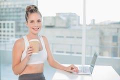 使用膝上型计算机的微笑的运动的金发碧眼的女人拿着咖啡 库存照片