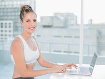 使用膝上型计算机的微笑的运动的金发碧眼的女人 免版税库存照片