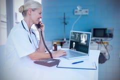使用膝上型计算机的微笑的医生的综合图象,当谈话在电话时 库存图片