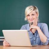 使用膝上型计算机的微笑的年轻老师在学校 库存照片