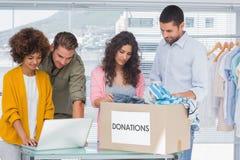使用膝上型计算机的志愿者和采取从慈善箱子的衣裳 免版税库存图片