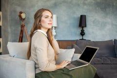 使用膝上型计算机的快乐的妇女 冲浪的万维网 库存照片