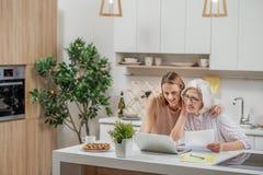 使用膝上型计算机的快乐的家庭在家 库存图片