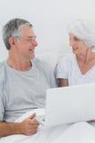 使用膝上型计算机的快乐的成熟夫妇 免版税库存图片