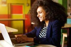 使用膝上型计算机的快乐的年轻非洲妇女在咖啡店 免版税库存图片