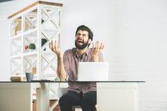 使用膝上型计算机的恼怒的愤怒的买卖人 库存图片