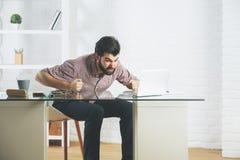 使用膝上型计算机的恼怒的愤怒的商人 免版税图库摄影