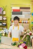 使用膝上型计算机的愉快的亚裔男性卖花人在柜台在花店 库存图片