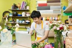 使用膝上型计算机的愉快的亚裔男性卖花人在柜台在花店 库存照片