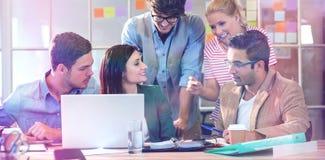 使用膝上型计算机的愉快的创造性的企业队在会议 免版税库存照片