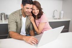 使用膝上型计算机的愉快的夫妇在厨房里 免版税库存照片