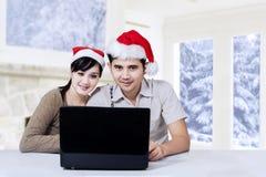 使用膝上型计算机的愉快的夫妇在圣诞节 库存照片