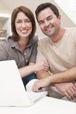 使用膝上型计算机的愉快的夫妇在家 免版税图库摄影