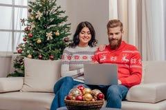 使用膝上型计算机的愉快的夫妇,当坐在圣诞节时的沙发 免版税库存图片