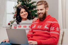 使用膝上型计算机的愉快的夫妇,当坐在圣诞节时的沙发 库存照片