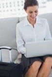 使用膝上型计算机的愉快的女商人 免版税图库摄影