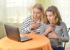 使用膝上型计算机的愉快的女孩和祖母 图库摄影
