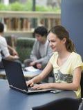使用膝上型计算机的愉快的女孩在图书馆 库存照片