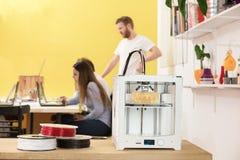 使用膝上型计算机的愉快的女性设计师由3D打印机在演播室 图库摄影