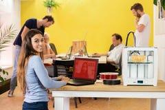 使用膝上型计算机的愉快的女性设计师由3D打印机在演播室 免版税图库摄影