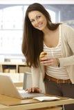 使用膝上型计算机的愉快的妇女吃新月形面包 免版税库存图片