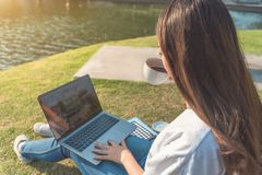使用膝上型计算机的愉快的妇女在公园,故意地被定调子 库存图片