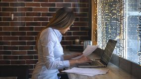 使用膝上型计算机的愉快的妇女在咖啡馆 坐在咖啡店和研究计算机的年轻美丽的女孩 股票视频