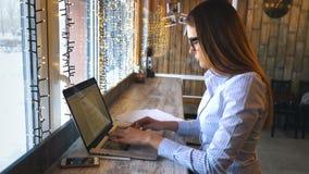 使用膝上型计算机的愉快的妇女在咖啡馆 坐在咖啡店和研究计算机的年轻美丽的女孩 股票录像