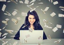 使用膝上型计算机的愉快的妇女建立网上事务根据倒下的美金 免版税图库摄影