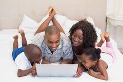 使用膝上型计算机的愉快的家庭一起在床上 免版税库存照片