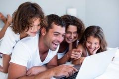 使用膝上型计算机的愉快的家庭一起在床上 库存图片