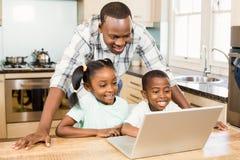 使用膝上型计算机的愉快的家庭在厨房里 库存图片