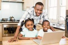使用膝上型计算机的愉快的家庭在厨房里 免版税图库摄影