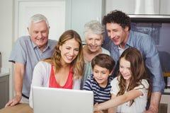 使用膝上型计算机的愉快的家庭在厨房里 免版税库存图片