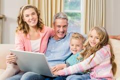 使用膝上型计算机的愉快的家庭在沙发 免版税库存照片