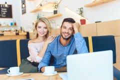 使用膝上型计算机的愉快的年轻夫妇和微笑对照相机 库存照片