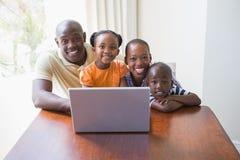 使用膝上型计算机的愉快的微笑的家庭 库存照片